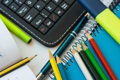 Draufsichtschulbedarf, Laptoptablettentastatur, mehrfarbige Bleistifte, Leuchtmarker, Stift, öffnete Mathematikarbeitsbuch mit Fo Stockbilder