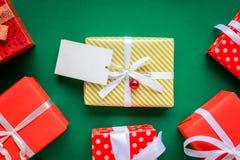 Draufsichtspott herauf weißen Textaufkleber und -Geschenkboxen auf dem grünen ta Lizenzfreie Stockfotos