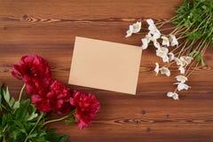 Draufsichtumschlag- und -frühlingsblumen auf hölzernem Hintergrund Lizenzfreie Stockfotos