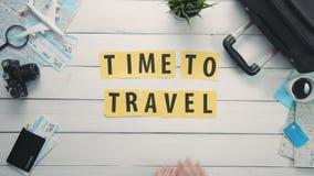DraufsichtZeitspanne übergibt das Legen auf weiße Schreibtischwort ` ZEIT, ZU REISEN das `, das mit Reiseeinzelteilen verziert wi stock video footage