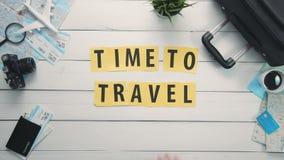 DraufsichtZeitspanne übergibt das Legen auf weiße Schreibtischwort ` ZEIT, ZU REISEN das `, das mit Reiseeinzelteilen verziert wi stock video
