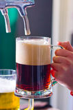 Draught beer. Glass being filled with draft beer Stock Photos