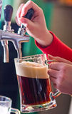 Draught beer. Glass being filled with draft beer by barman Royalty Free Stock Images