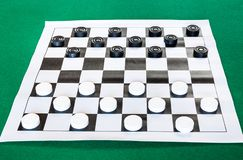 Draughts on black and white checkered sheet board. On green baize table stock photography
