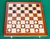 Draughts on wooden board on green table. Draughts on wooden checkered board on green baize table royalty free stock photo