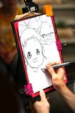 Draw. The portrait is drawn by a simple pencil a hand of the street Korean artist which draws a cartoon from people in the street Insadong in city of Seoul South Stock Image