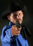 Draw. Menacing cowboy aiming revolver gun at camera Royalty Free Stock Image