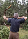 Draw a bow. Archer aiming at target to practice his hobby royalty free stock photos