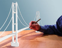 Draw Bridge. Architect drawing a suspension bridge in 3d on his desk Royalty Free Stock Photos