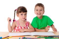Draw för två liten ungar med crayons royaltyfri bild