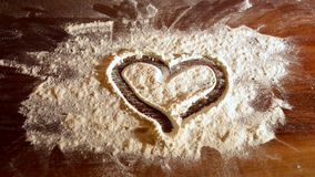 Draw heart of flour finger. Heart of flour on board. erase stock video footage