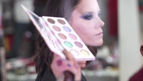 Draw lips and eyes. Makeup artist apply makeup to an attractive young model for photo session stock footage