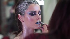 Draw lips. Makeup artist apply makeup to an attractive young model for photo session stock video