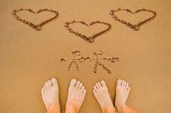 Draw romantic Love hearts on beach. Draw romantic Love heart and lover on beach and lover feet Stock Photography