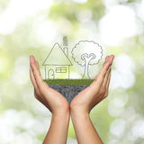 Draw shape of house on man hand in concept of residential and ho. Me building and have abstract green bokeh background stock photography