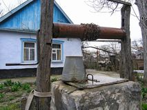 Draw well with metal bucket on chain as rustic water supply. Authentic Russian countryside life. Private peasants house and yard. Krasnodar, Russia - March 24 stock photo
