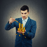 Draw your wealth. Creative businessman holding a pencil in his hand try to draw an imaginary wealth, golden coins in palm. Grey wall background Stock Photos