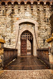 Drawbridge to Castle Door. A wooden drawbridge with chains leads to wooden doors and a metal gate entrance way of a medieval castle Stock Photo
