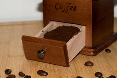 A drawer of a coffee mill with coffee powder and some coffee beans. Photographed with macro lens royalty free stock photo