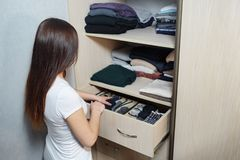 The drawer with underwear in the closet. Girl organizing clothes in wardrobe, close up stock images