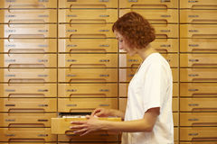 Drawers in medicine cabinet. Pharmacist reaching for drawer at medicine cabinet royalty free stock photography