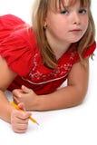 Drawin pequeno da menina algo com um lápis isolado fotos de stock