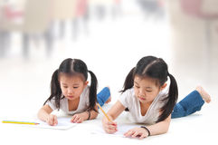 Drawing. Little Asian girls drawing, lying on floor stock photos