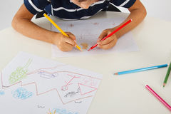 Drawing. Little boy drawing pictures on the table Royalty Free Stock Photos