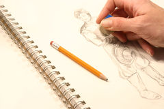 Drawing. Hand with an eraser, erase a detail on a theater character draw Stock Photos