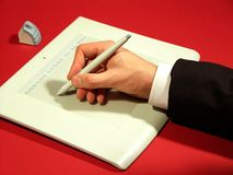 Drawing. Hand drawing on a graphic tablet. Hand in focus. White shirt and black suit royalty free stock photos