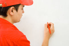 Drawing. A young man drawing - whatever you want to place there - on the half prepared wall (focus on the pencil Royalty Free Stock Images
