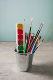 Drawing accessories - pencils, paints and brushes on a gray back Stock Images