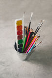 Drawing accessories - pencils, paints and brushes on a gray back Stock Photo