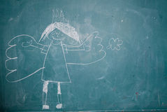 Drawing of angel princess on chalkboard by child stock image