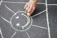 Drawing on asphalt. Hand drawing the sun a chalk on asphalt Stock Images