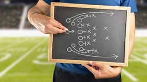 Drawing Attack Tactics. Hand of a american football coach drawing a tactics of game with white chalk on blackboard at stadium background stock photo