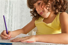 Drawing with attention. Little girl making a drawing with colored pencils stock image