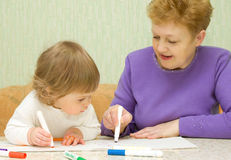 Drawing baby with her grandma. At home Royalty Free Stock Photos