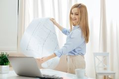 Inspired woman holding a big drawing. Drawing. Beautiful inspired young blond woman holding a big drawing and looking at the screen of her laptop while standing Royalty Free Stock Images