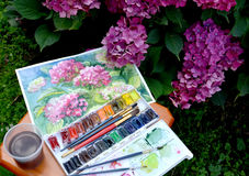 The drawing  Blossoming Hydrangeas, water color paints and flowers in a garden. The drawing Blossoming Hydrangeas, water color paints and flowers in a garden Stock Photos