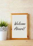 Drawing board with the phrase welcome aboard handwritten over wooden table. Royalty Free Stock Photo