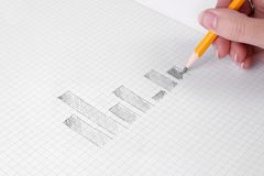 Drawing business charts. Human hand drawing business charts with a pencil on graph paper Stock Image