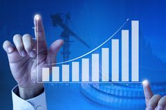 Drawing business growth and rapid success. Close up of a businessman's hands expanding an exponential line curve and bar chart showing of business growth stock photo