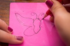 Drawing a Butterfly. A girl drawing a picture of a butterfly stock photo