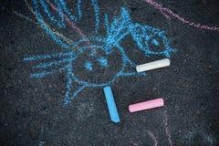 Drawing of a cat chalk on asphalt. Colorful chalk drawing on asphalt: funny cat. Drawing of a cat chalk on asphalt royalty free stock photo