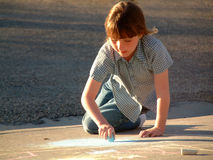 Drawing with Chalk. Little girl drawing on sidewalk with chalk Stock Photo