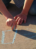 Drawing with Chalk. Closeup of hands drawing on sidewalk with chalk Stock Photography