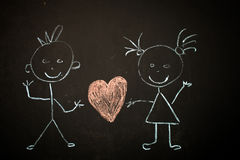 Drawing with chalk on black Board. Girl with boy stock image