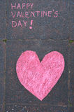 Drawing in chalk Happy Valentine's day. Drawing in chalk on a pavement; a pink heart and Happy Valentine's day notice royalty free stock photography