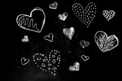 Drawing chalk hearts. On a black background, the concept of friendship stock photography